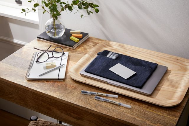 small desk with wood tray, laptop, pens, notebook, glasses and a vase with a plant set on stack of notebooks