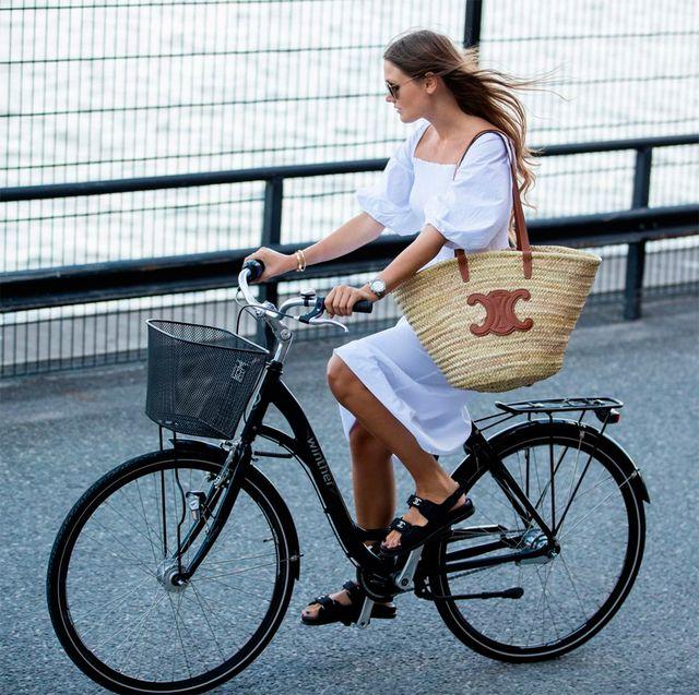 mujer con bolso de rafia en bici