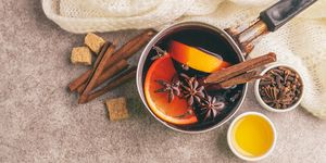 Hot mulled wine in a small vintage pan with ingredients on the gray slate background