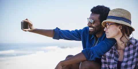 Multi-ethnic couple taking selfie on sunny summer beach
