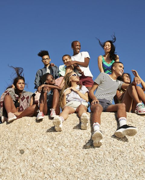 multi ethnic friends sitting together on rock