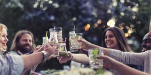 Multi-ethnic friends toasting mojito glasses at dinner table in yard