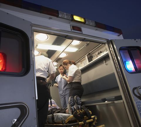 Multi-ethnic medical professionals with patient in ambulance