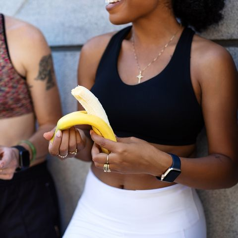 multiethnic women eating banana after training session