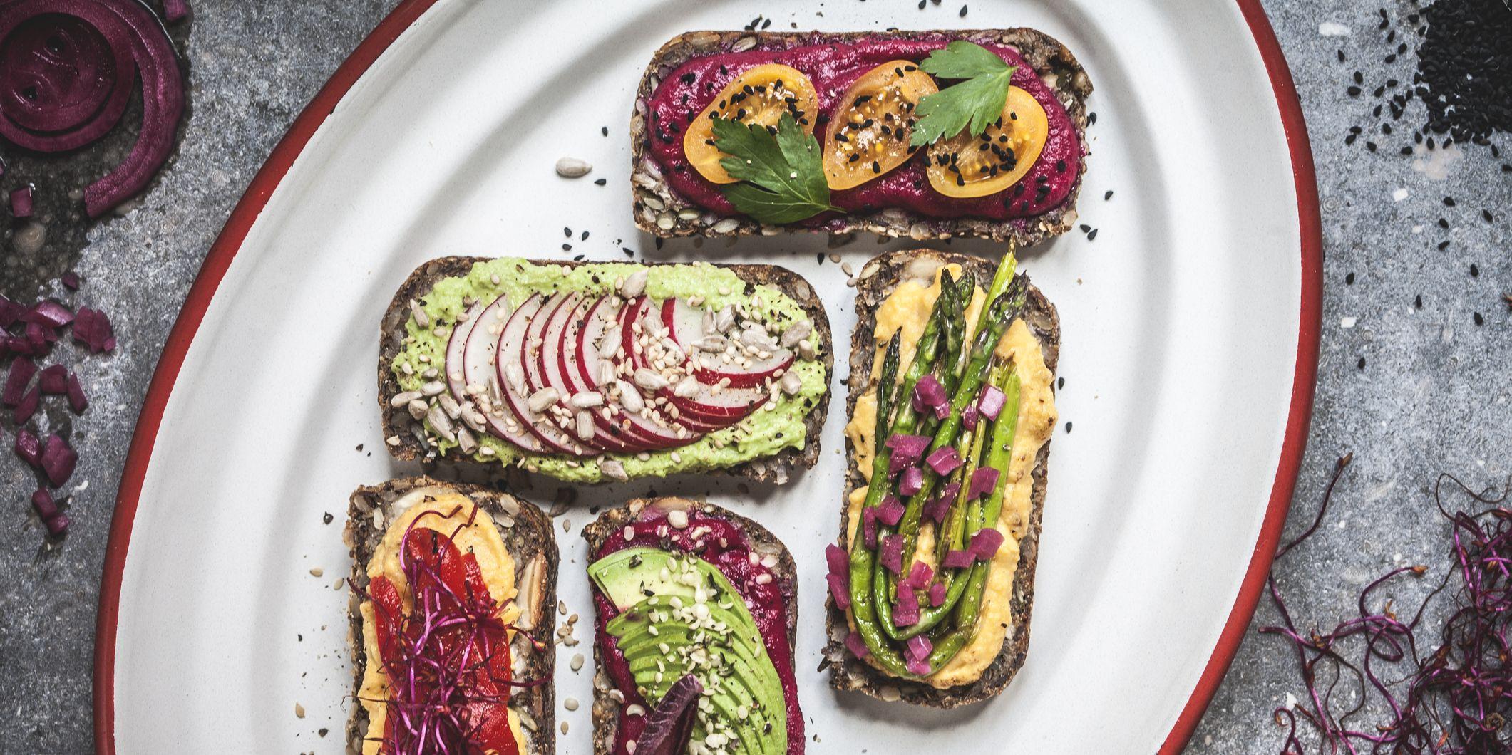 Multicoloured hummus on toasts Vertical