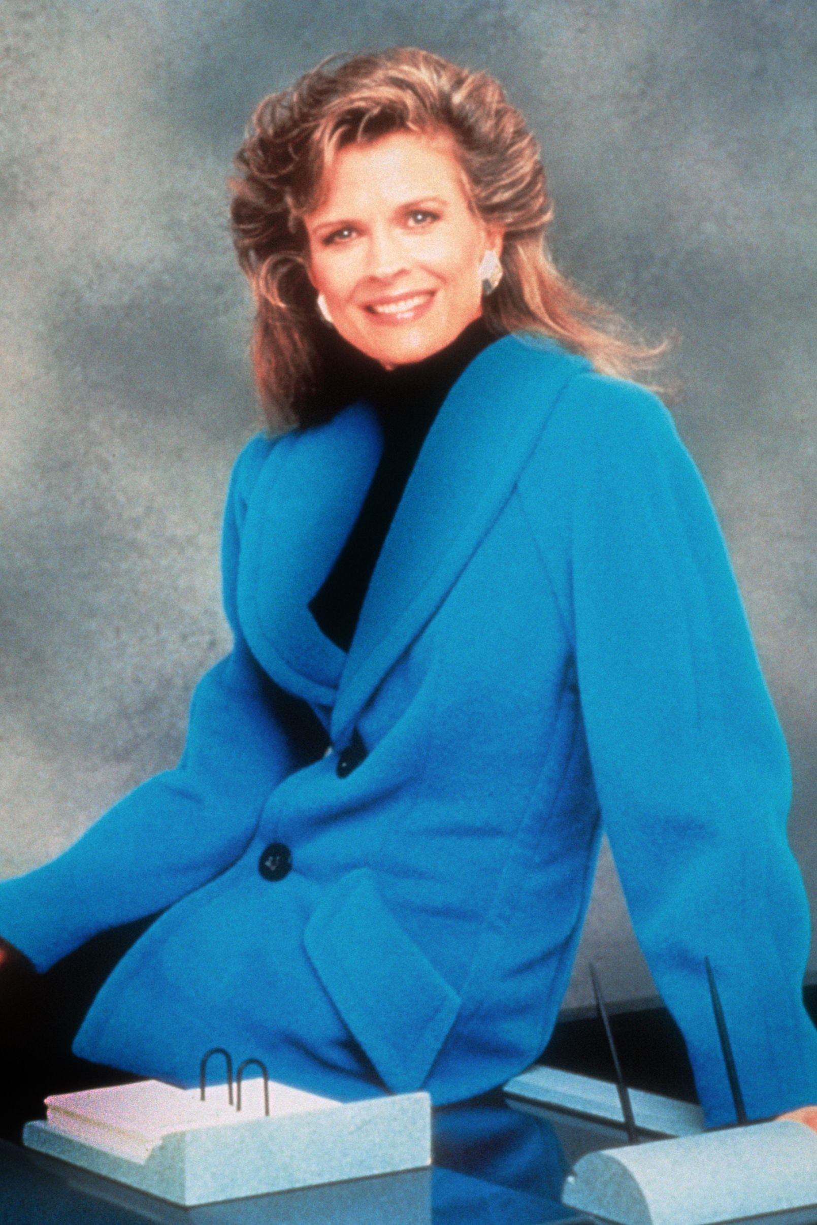 Candice Bergen Seated On A Desk With A Blue Jacket