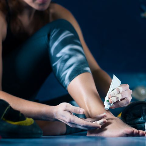 muscle female woman treats wounds after climbing bouldering in training hall