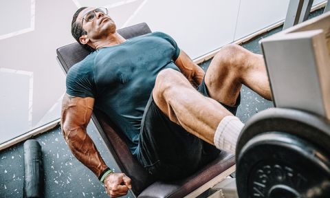Muscle man trains legs on gym machine. Fitness