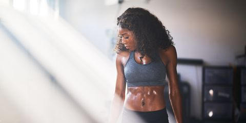 muscular african american woman sweating from work out in home gym