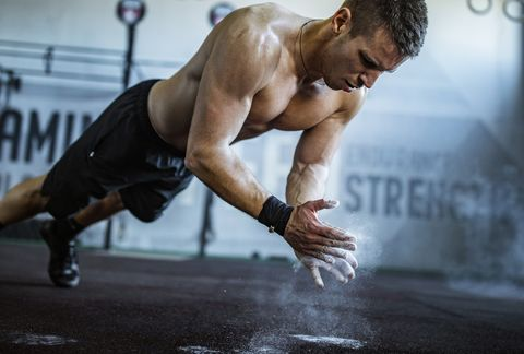 Muscular build athlete having cross training in a gym.