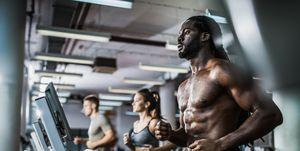 Muscular build black man warming up on treadmill in a health club.