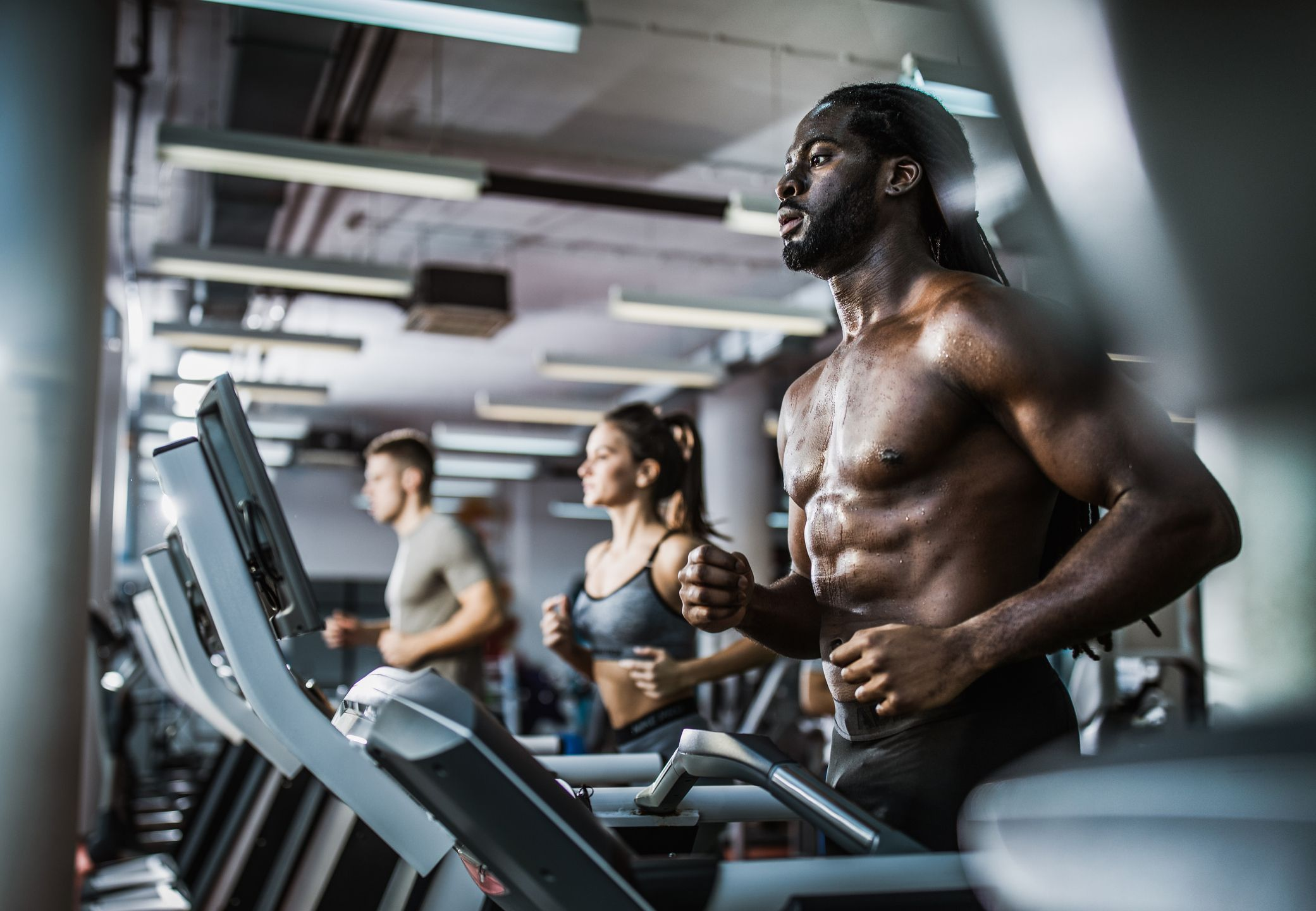 treadmill workout lose belly fat and build musclemuscular build black man warming up on treadmill in a health club