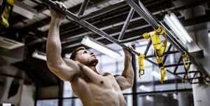 Muscular build man exercising chin-ups in a gym.