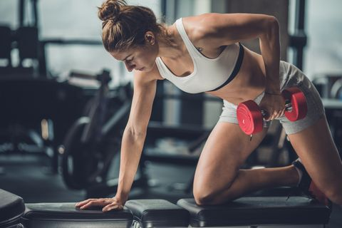 Muscular build woman exercising with dumbbells in a health club.