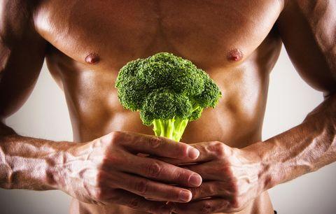 Muscular Caucasian athlete holding broccoli