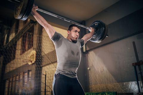 muscular man deadlifting barbell