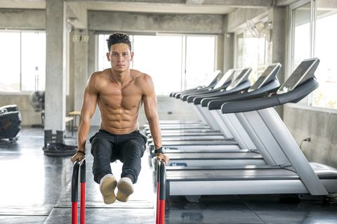 muscular man doing l sit position on parallel bars workout at gym healthy lifestyle, exercising and people concepts