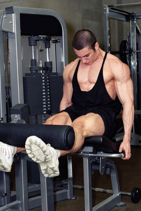 Muscular man doing legs workout in fitness club