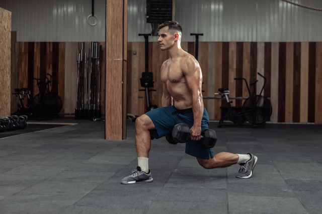muscular man training his legs, doing lunges with heavy dumbbells in modern gym healthy lifestyle concept