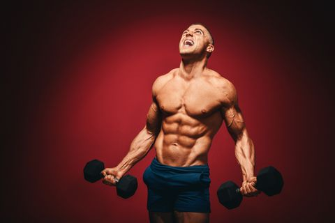 Muscular man with dumbbells screaming in pain