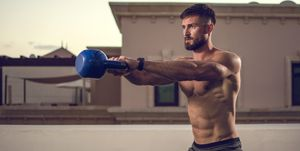 Muscular shirtless sportsman training with kettlebell outdoors