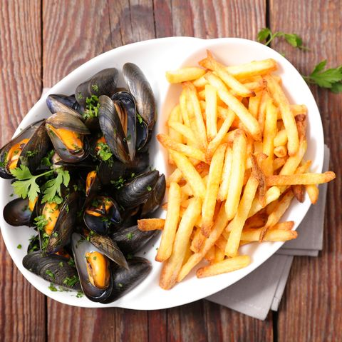 mussel and french fries on wood background