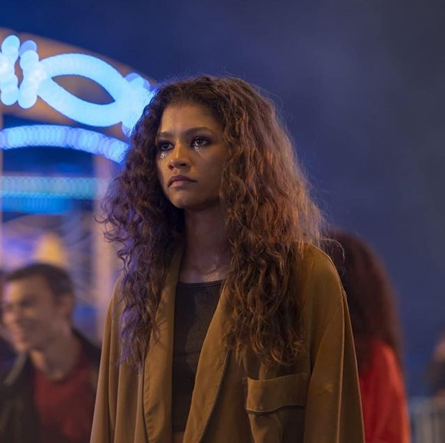 zendaya shooting a scene for euphoria she's standing in a carnival, and you can see the lights of the carnival rides behind her