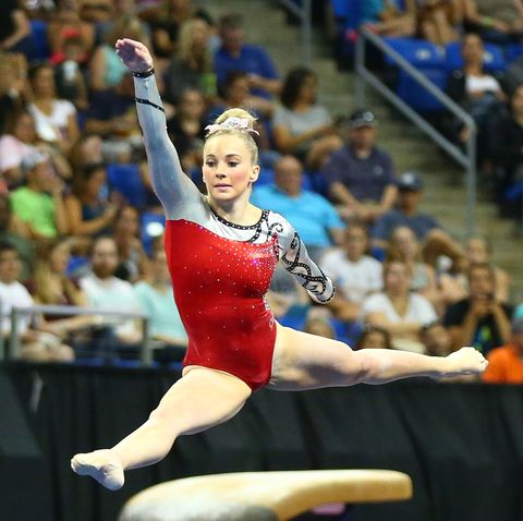 mykayla skinner leaping across the floor in a red leotard and a white and pink bow in her hair