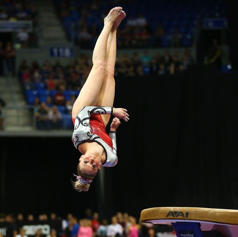 mykayla skinner in midair over the vault in a red sparkly leotard and bow in her bun