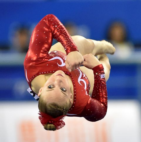 mykayla skinner upside down on the mat in midair wearing a re sparkly leotard