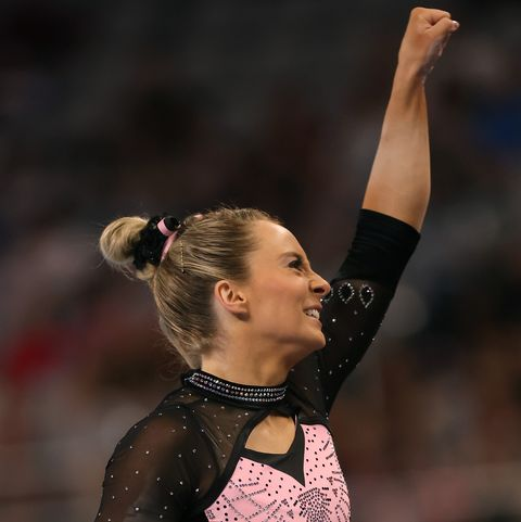 mykayla skinner fist pumping in a black and pink sparkly leotard