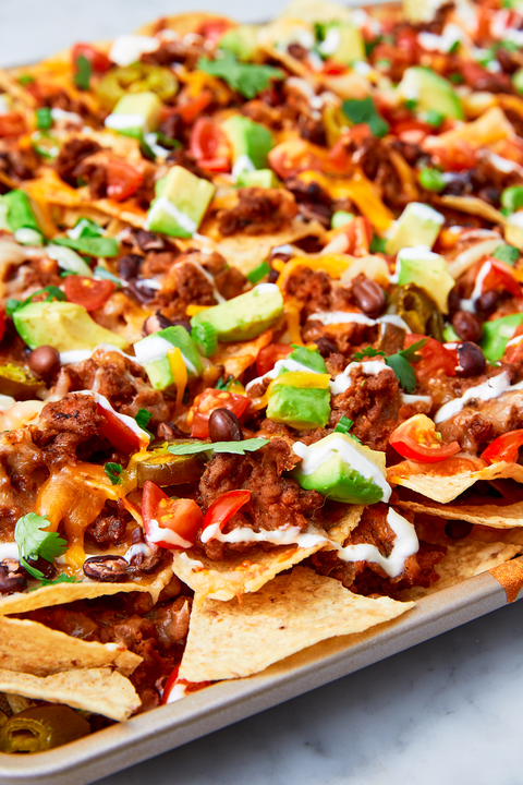 nachos covered with multiple toppings and cheese