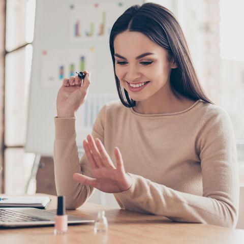 Portrait of fashionable stylish modern dreamy careless excited satisfied elegant attractive charming gorgeous financier applying varnish on nails sitting at the desktop reception room