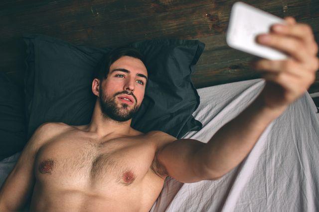 naked bearded dark hair handsome man shirtless in white bed taking a selfie