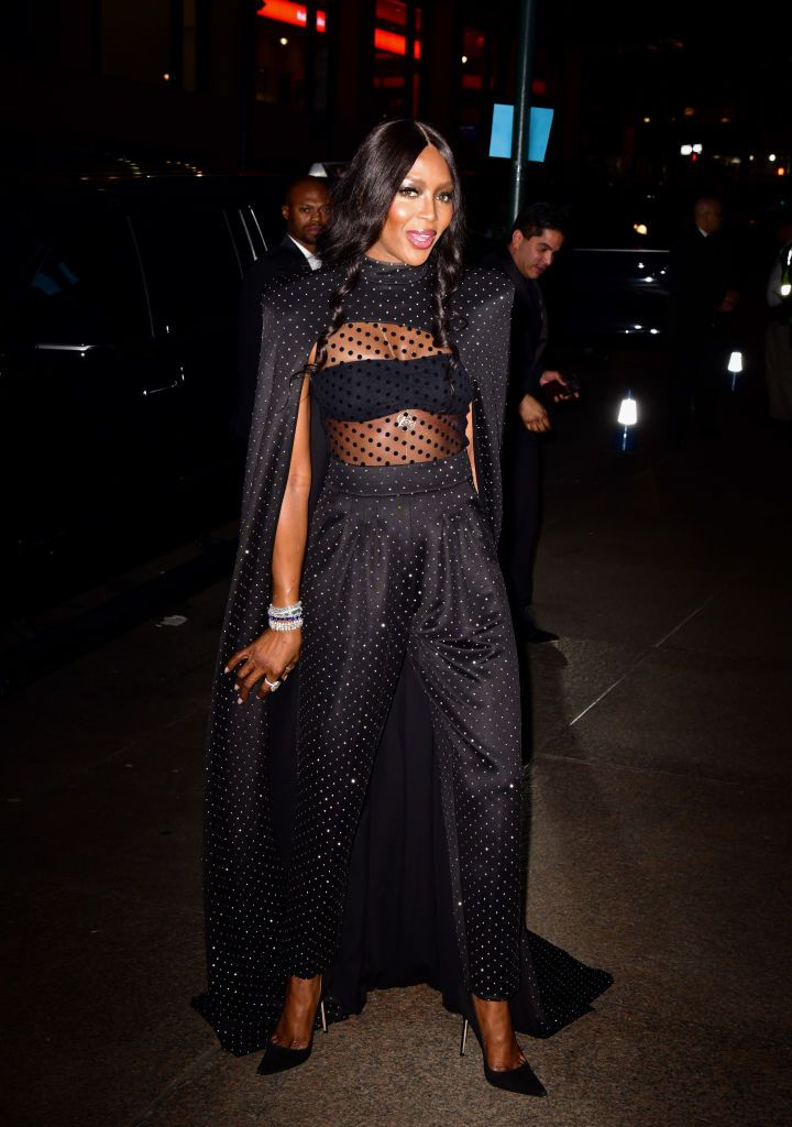 The supermodel arrived wearing a bejeweled cape by Balmain .