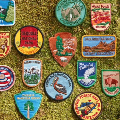 an assortment of vintage national parks patches shot on a grassy surface
