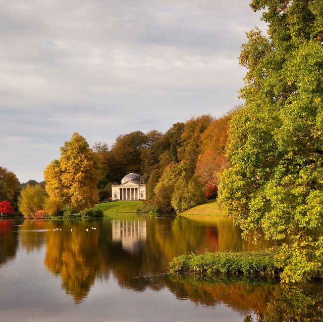 in autumn, a view across the lake to the pantheon at stourhead gardens, wiltshire, uk