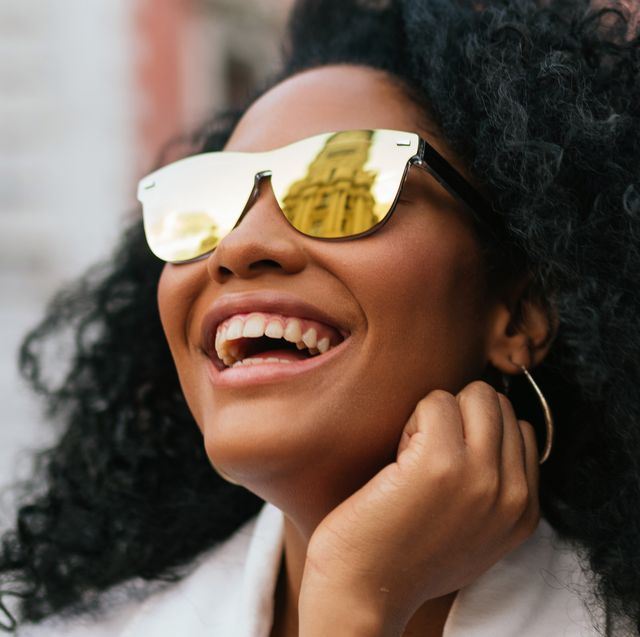curly-haired woman smiling with sunglasses