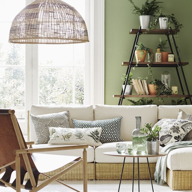 a low white sofa, with scattered green and white patterned cushions, in a white room, with a large french doors, wooden shelves with black metal poles, holding brown and silver pots of green plants, books and ornaments, and a brown fold out chair underneath a large, woven lampshade walls painted in yeabridge green estate emulsion, £3950 for 25l, farrow  ball bowen rattan seats with cushions, £295 each bowen rattan ottoman with cushion, £195 all habitat lounge chair, £895 alburni table, £462 indah hide rug, £835 all heal's a line shelf, £550, graham and green rattan shade, £70, habitaton sofa l r kulgam greywhite cushion cover, £49, luma botanist embroidered cushion, £14, sainsbury's haveli cushion cover, £49, luma syssan cushion, £12, ikea linen lines cushion, £1999, zara home alpaca blend throw, £90, northlight homestore on coffee table tumblers, £8 each tequila jug, £70 all heal's on top shelf pots, £21 for three, rockett st george on second shelf pot, from £1, dobbies vintage bottles, find similar at home barn ingefära plant pot, from £150 for 105cm dia, ikea heritage twine, £350, paperchase third shelf socker plant pot, from 95p for 105cm dia, ikea faux deer skull in dome, £69, rockett st george