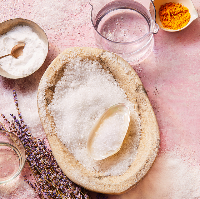 salt, lavender, and turmeric spice sprinkled over pink background