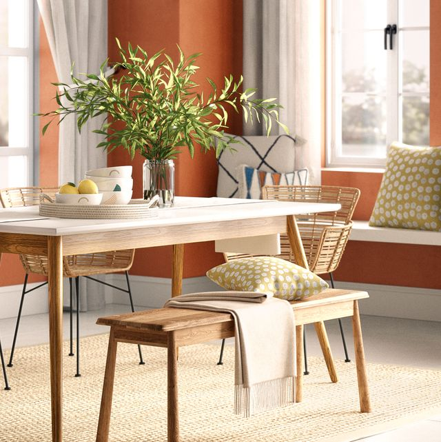 dining room with orange walls, wooden furniture and a nature inspired theme