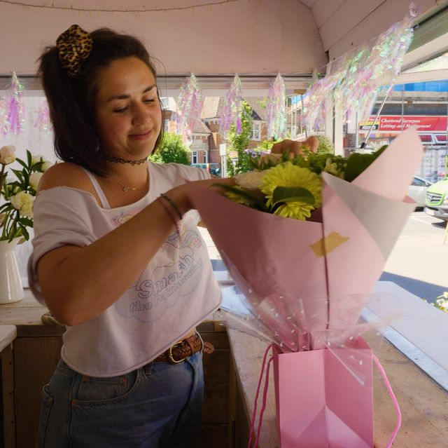 alice holding a bouquet of flowers inside her pink horsebox