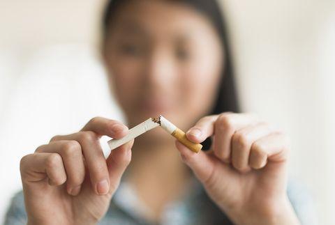 Mixed race teenage girl breaking cigarette in half