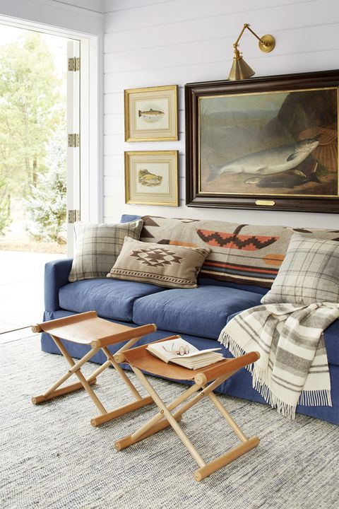 rustic living room with blue sofa, leather stools, and fish artwork