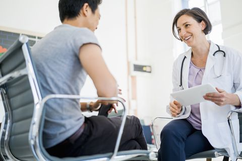a photo of happy doctor holding digital tablet while looking at patient female medical professional is communicating with man they are sitting on chairs in clinic