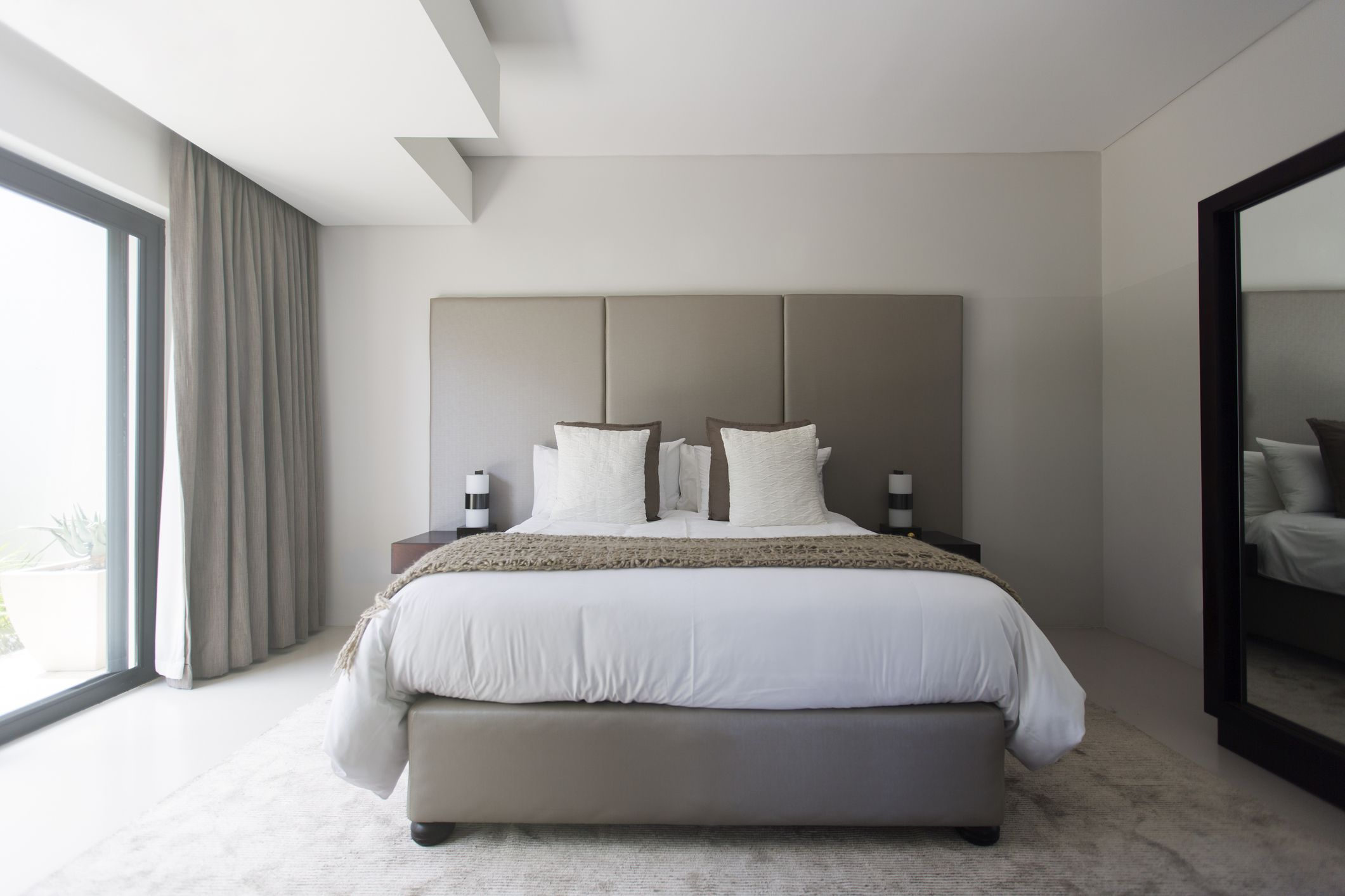 Modern white and beige bedroom with double bed