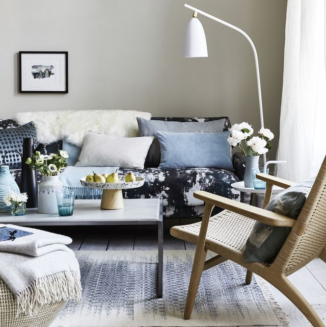 sitting room with cushions on the blue patterned sofa, a white floor lamp bent over the sofateamdrips, spotsandsplatter patterns foranimpressionistic look that'scontemporary andrelaxed