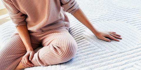 woman wearing pink ribbed pajamas sitting on new casper mattress