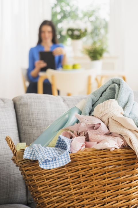 USA, New Jersey, Jersey City, Laundry basket on sofa and woman in background