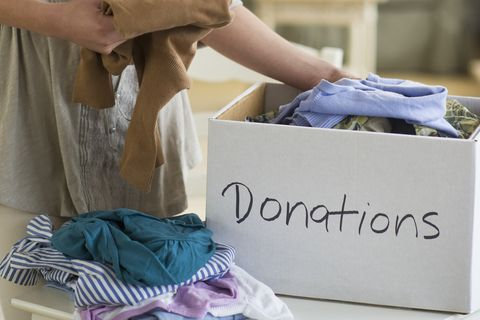 usa, new jersey, jersey city, woman preparing clothing for donation